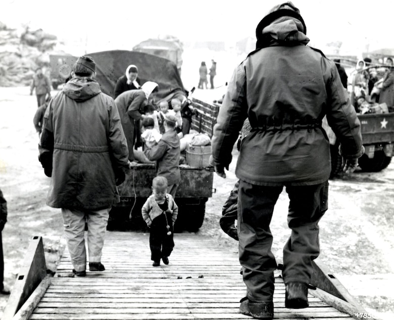A Korean toddler climbs aboard a C-54 bound for Cheju-do. (U.S. Air Force photo)