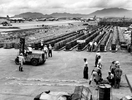 Supplies stand ready at an air base in Japan. This food and fuel will be loaded onto C-119s and dropped to front-line forces. (U.S. Air Force photo)