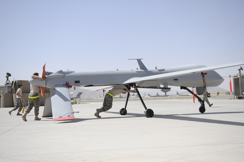 Members of the 451st Expeditionary Aircraft Maintenance Squadron unit push an MQ-1 Predator toward a hangar for a routine maintenance inspection shortly after landing. The remotely piloted aircraft are launched, recovered and landed by members of the 62nd Expeditionary Reconnaissance Squadron. The reconnaissance unit  is comprised of deployed Air Force members from the 432nd Operations Group, Creech Air Force Base, Nev., and the 27th Special Operations Group, Cannon AFB, N.M. Additionally, the British Royal Air Force also operates RPAs from Creech AFB and they too are deployed to KAF. (U.S Air Force photo by Senior Airman Nancy Hooks)