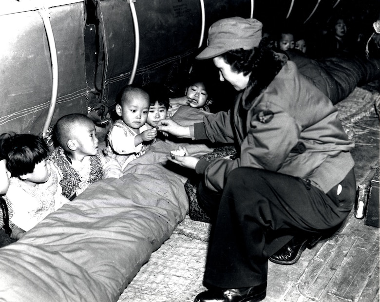 Flight nurse Capt. Mary Spivak hands out candy to orphans during the evacuation. (U.S. Air Force photo)