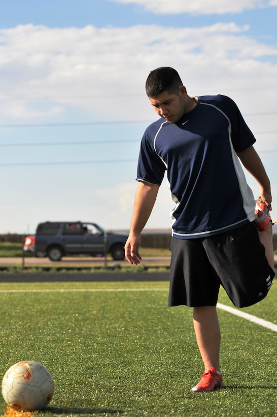 BUCKLEY AIR FORCE BASE, Colo. -- Airman 1st Class Nolan Luna-Chavez,460th Space Communication Squadron, stretches before doing a few practice drills. Airman Luna-Chavez has been playing soccer since the 7th grade. (U.S. Air Force photo by Airman 1st Class Paul Labbe)