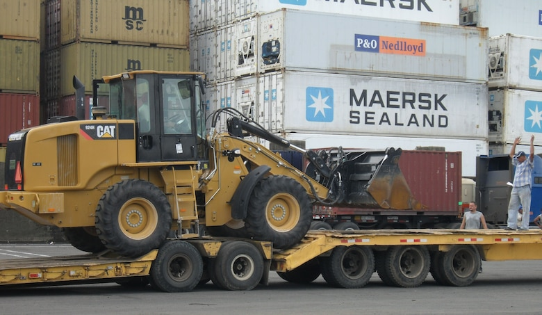 Airmen load a bulldozer onto a flatbed in preparation to leave the port in Panama City. More than 200 pieces of cargo were transported to Meteti, Panama, the site for New Horizons Panama 2010, a 12-week humanitarian assistance mission. More than 250 Airmen, Soldiers and Marines will deploy to six constructions sites and five medical missions in Panama. (U.S. Air Force photo/Staff Sgt. Teresa Burger)