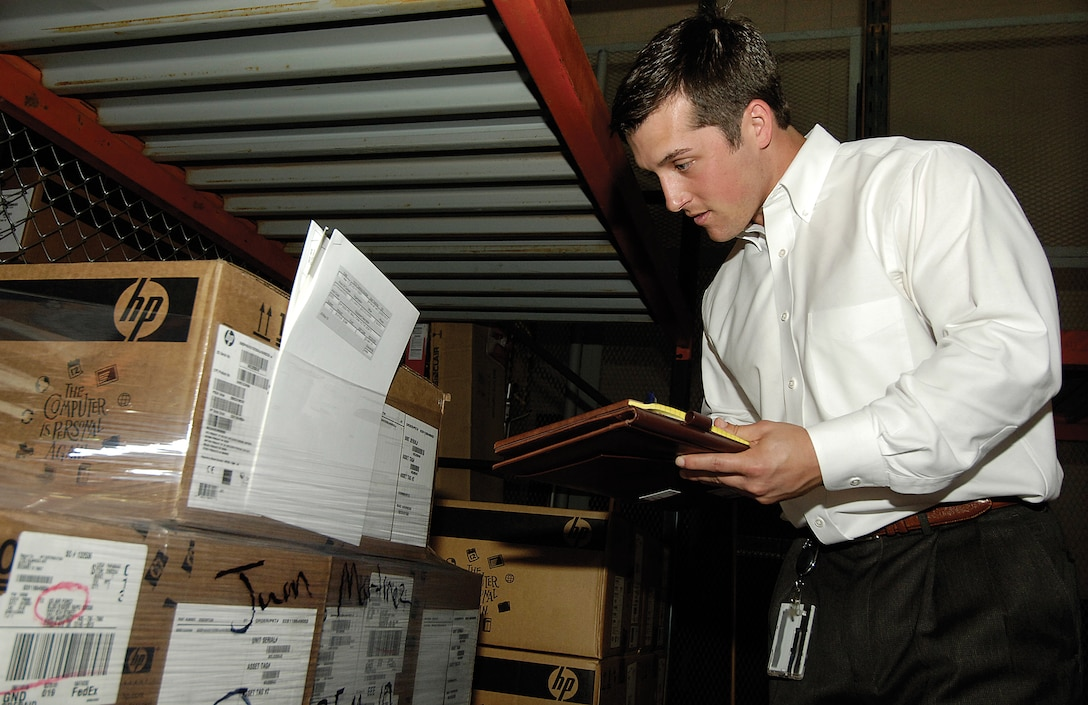 Taylor Lamar checks records, verifying equipment in a 72nd Air Base Wing supply warehouse.  Auditors may specialize in certain areas but all are cross trained to audit areas from the golf course to propulsion, and the chapel to small arms weapons. (Air Force photo by Margo Wright)