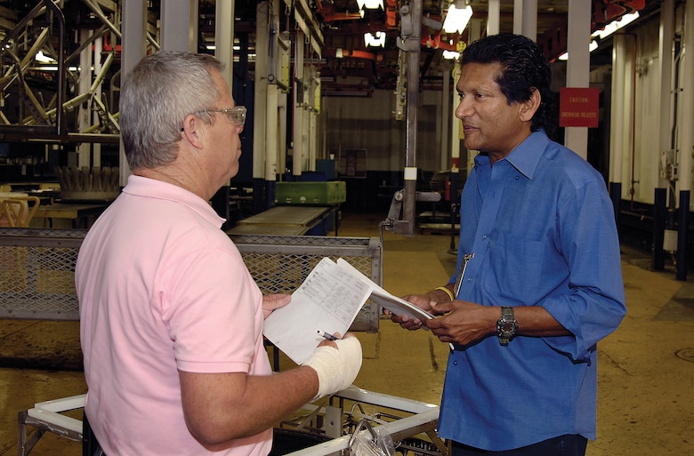 """Air Force Audit Agency's Bala Aurobinda, right, often works in Bldg. 3001 and enjoys working with people in a wide variety of shops. """"I try to help people and make processes better,"""" he said about his role as an auditor. In the Case Non-Destructive Inspection shop of the 548th Propulsion Maintenance Squadron, Mr. Aurobinda and NDI supervisor Mark Wilson discuss records.(Air Force photo by Margo Wright)"""