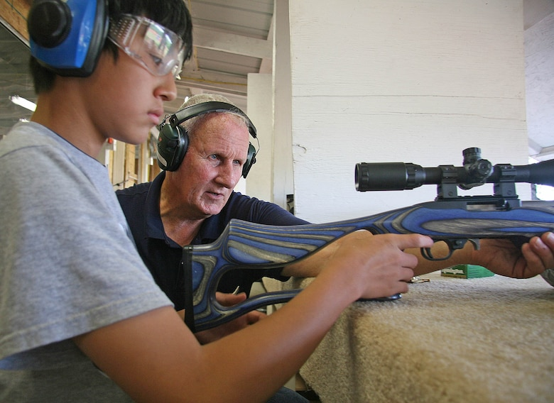 Former Marine Corps marksmanship trainer Ken Caudle, right, gives some .22 rifle instruction to James Gallaher, 14, during a recent Tinker Shooting Club gathering. Gallaher's father, Willard, works at Tinker and said the club has given his family a great start into the sport of shooting. (Air Force photo by John Stuart)