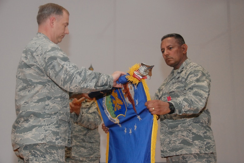 SOUTHWEST ASIA - From left, Col. John R. Gordy II, 386th Air Expeditionary Wing commander, and Col. Jorge Acevedo, the last 586th Air Expeditionary Group commander, furl the 586th AEG guidon during the group's inactivation ceremony here June 17, 2010 at an undisclosed air base. (U.S. Air Force photo by Staff Sgt. Lakisha A. Croley/Released)