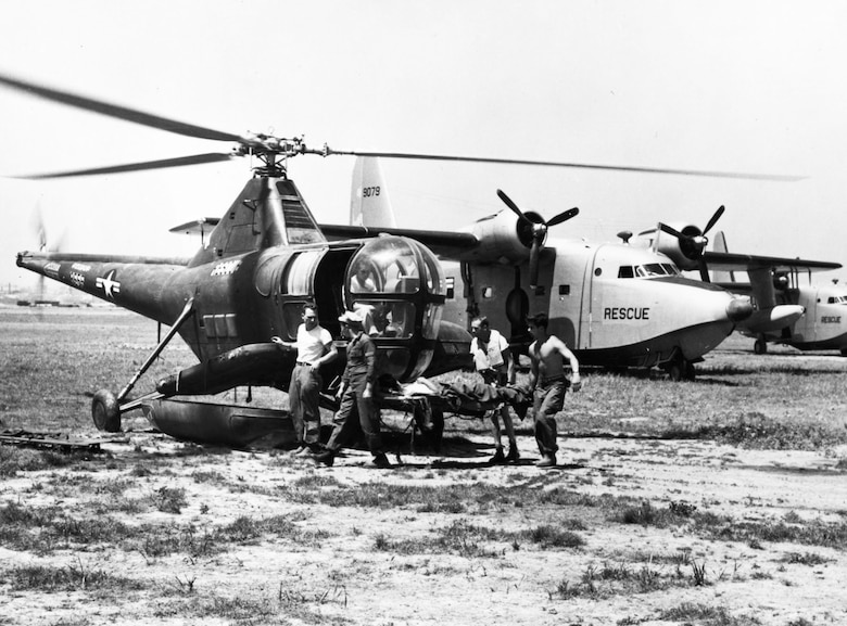 Helicopters and seaplanes worked together. Here, Airmen transfer a patient from the SA-16 Albatross amphibian in the background to an H-5G helicopter. (U.S. Air Force photo)