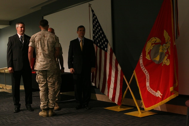 A graduate of the U.S. Marine Corps Forces, Special Operations Command Advanced Linguist Course receives his diploma during a ceremony at the MARSOC headquarters building, June 17. Ten Marines graduated from the MARSOC ALC 52-week long Dari, Pashtu and Urdu courses.