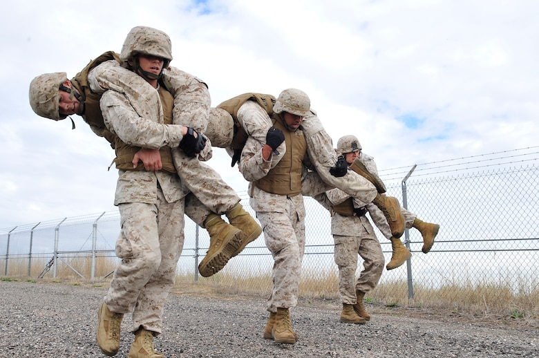 BUCKLEY AIR FORCE BASE, Colo. --Macs-23 Marines(left to right) Sgt Randall Blankenship, SSgt Albert Martinez, Cpl Charles Bays carries fellow Marines (left to right) Sgt. Dale S Steinecke, Cpl Trent Wilcox , Sgt Joshua Tucker as part of there Combat Skills training.Marine members take a three week Marine Corps Martial Arts Program course.(U.S Air Force photo by Airman 1st Class Paul Labbe)