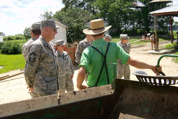 An Amish boy on his family's farm in northeast Iowa teaches Chief Master Sgt. Don Kuehl, left, and other members of the Iowa National Guard's 734th Agri-Business Development Team the finer points of using a manure spreader hauled by draft horses.