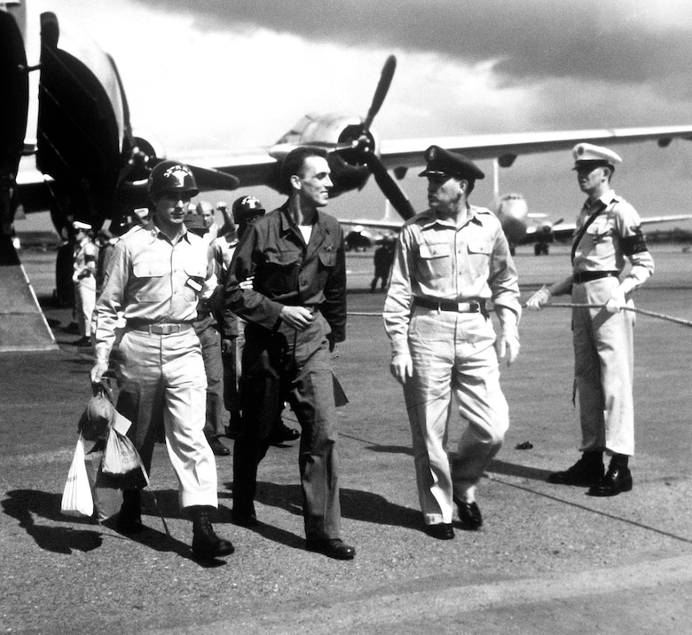 One of the first Air Force POWs to return to Japan in Operation Big Switch was Staff Sgt. Robert M. Wilkins (center). He is shown arriving in Japan after the 4-and-a-half hour flight from Korea, Aug. 18, 1953.  (U.S. Air Force photo)