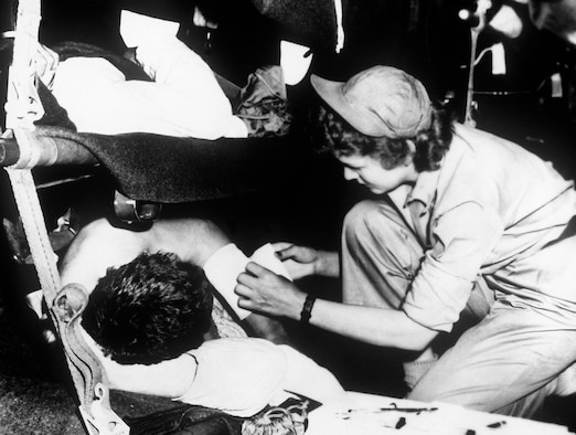 Flight nurse 2nd Lt. Pauline Kircher dresses a patient's wound during the flight from Korea to Japan, May 1951. (U.S. Air Force photo)