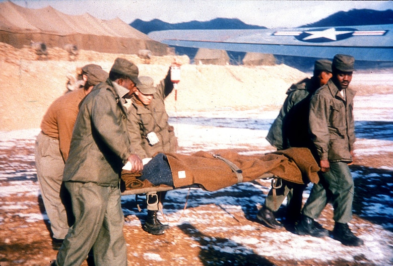 Airmen move a wounded patient. Speedy evacuation by air cut the casualty death rate by half from World War II. (U.S. Air Force photo)