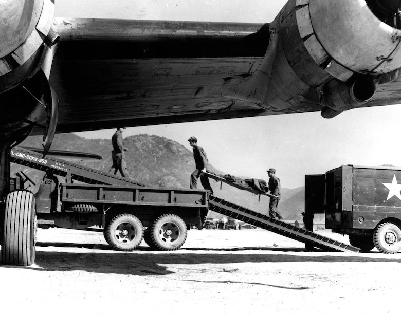 Airmen carry litter patients up truck ramps and into transport aircraft. (U.S. Air Force photo)