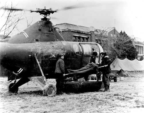 An H-5 crew delivers a wounded soldier to a MASH (Mobile Army Surgical Hospital) unit. (U.S. Air Force photo)
