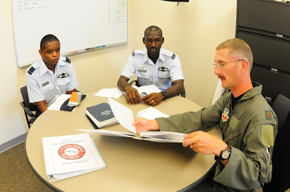 North Dakota Air National Guard pilot Maj. Steven Larson, right, explains aspects of U.S. Air Force pilot training June 21, with visiting Ghanaian Air Force pilots Flying Officer Peter Attah-Obeng, left, and Flight Lieutenant Felix Kattah at the Fargo, N.D. Air National Guard flying wing.  The pilots are interacting as part of the state partnership program between the North Dakota National Guard and the African country of Ghana.