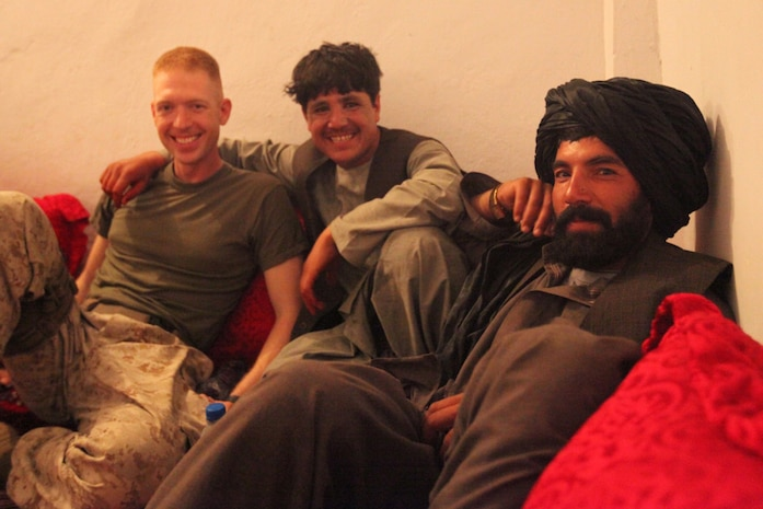 Abdul Gunny, Kharshma, and Cpt. Phillip Noack, a civil affairs team leader with 1st Battalion, 2nd Marine Regiment, Regimental Combat Team 2, pose for a picture during a party with Afghan National Police and Marines, June 23. Noack, who will be leaving Musa Qal'eh, was the guest of honor. The party began with a meal of beans, rice, beef, and French fries. After the meal, a few of the ANP played live music and Abdual Gunny sang. The ANP and Marines were having a good time and even danced to the music. The friendships created through interactions like this will help the Afghan police force and Marines work better together.  ::r::::n::(Official U.S. Marine Corps photo by Cpl. Ned Johnson)