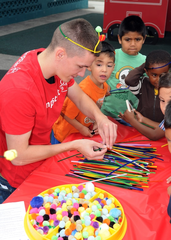 A volunteer from the 61st Communications Squadron helps children at the Inglewood Child Development Center make antenna out of pipe cleaners, June 22.  (Photo by Jim Gordon)