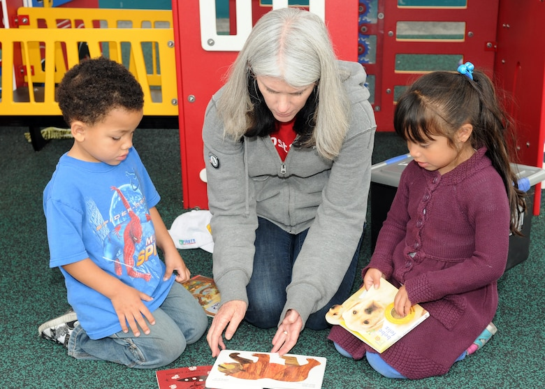 A volunteer from the 61st Communications Squadron reads to children at the Inglewood Child Development Center, June 22.  The center is run by the Inglewood Unified School District and provides programs for preschoolers, ages 3 to 5. (Photo by Jim Gordon)