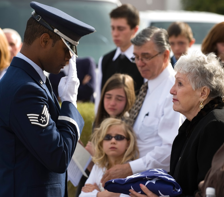 LAS VEGAS, Nev.-- US Air Force Staff Sgt. Julio Viloria salutes a funeral flag after handing it off to a widow during a performance of military funeral honors at Palm Mortuary in Las Vegas, March 18, 2010. (U.S. Air Force Photo / Airman 1st Class Jamie Nicley)