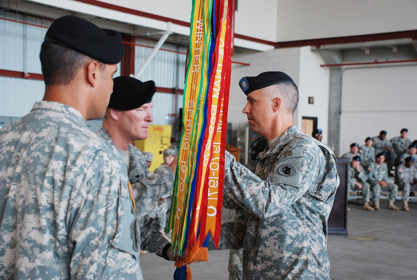 SOTO CANO AIR BASE, Republic of Honduras -- Col. Gregory Reilly, the Joint Task Force-Bravo commander, passes the guidon to Lt. Col. James Kanicki during a change of command ceremony here June 24. In accepting the colors symbolizing the 1st Battalion, 228th Aviation regiment, Colonel Kanicki took command of the unit from Lt. Col. Salome Herrera Jr. (left).  (U.S. Air Force photo/Tech. Sgt. Benjamin Rojek)