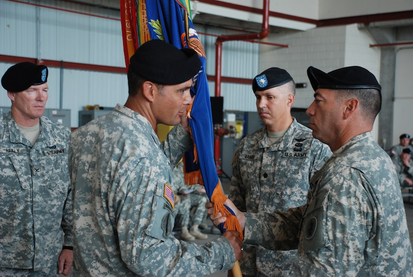 SOTO CANO AIR BASE, Republic of Honduras -- Lt. Col. Salome Herrera Jr. takes the guidon from Command Sgt. Maj. Lucio DeAnada during a change of command ceremony for the 1st Battalion, 228th Aviation Regiment here June 24. As is tradition, Colonel Herrera then passed the colors to Col. Gregory Reilly, the Joint Task Force-Bravo commander, who in turn passed the colors to the unit's new commander, Lt. Col. James Kanicki. This change of command tradition dates back to the 17th century. (U.S. Air Force photo/Tech. Sgt. Benjamin Rojek)