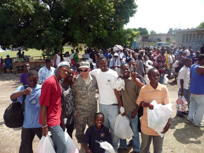 Master Sgt. Craig DeLorme, a pest management supervisor with the 128th Air Refueling Wing's Civil Engineering Squadron, Milwaukee, WI, stands with Haitians holding bags of food in Port-au-Prince, Haiti.  DeLorme deployed to Haiti on Feb. 23, 2010, to assist in the relief effort by reducing the pestilence in the affected area and helping to ensure clean water was available.  (photo submitted by Master Sgt. Craig DeLorme)