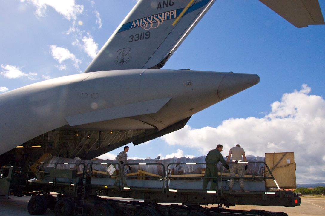 The 40-foot mast that was originally attached to USS Oklahoma is loaded on a C-17 on its way from Joint Base Pearl Harbor-Hickam to Muskogee War Memorial in Oklahoma. The battleship Oklahoma, named after the 46th state, was sunk during the Dec. 7, 1941 attack. The effort is part of a tribute to be made at the Muskogee War Memorial honoring the USS Oklahoma and her crew. (U.S. Air Force photo by Staff Sgt. Nathan Allen)