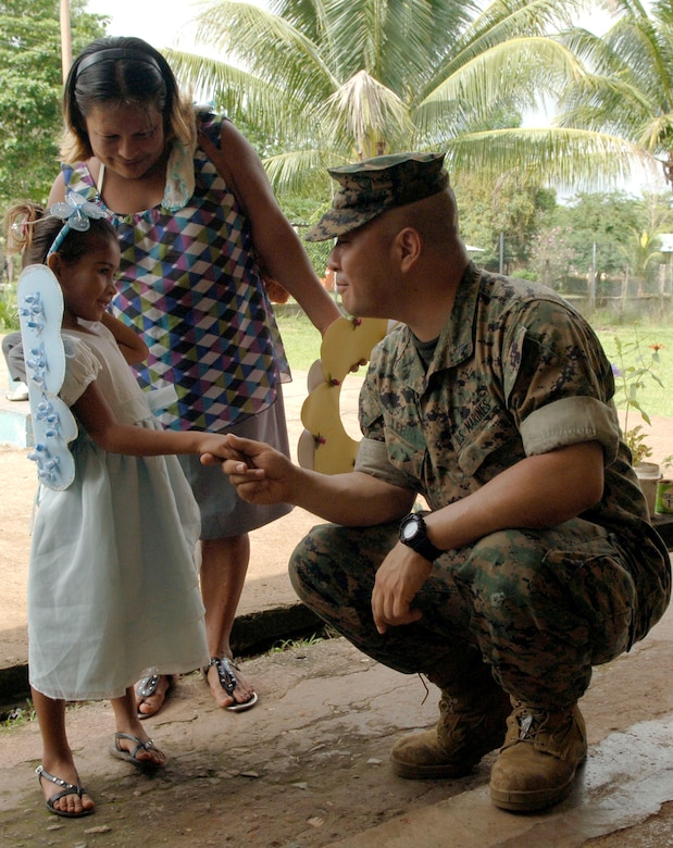 Cpl. Ellis Lee, Marine 4th Civil Affairs Group, introduces himself to a young girl and her mother at the Rio Iglesia elementary school June 24. Personnel from New Horizons Panama 2010 took time out of the construction schedule to support the school's conservation day festival. (U.S. Air Force photo/Tech. Sgt. Eric Petosky)