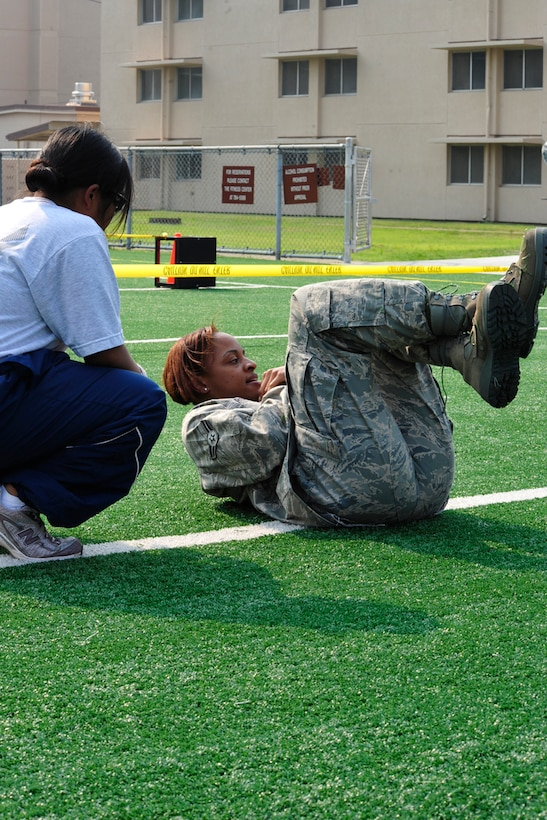 Airman 1st Class Teneil Roman, 51st Operation Support Squadron, completes crunches as a monitor keeps count during a Warrior Challenge competition, put on by the Osan Fitness Center. Throughout the competition four teams were timed as they completed several physical tasks. The team with the fastest time won trophies for each of its members. (U.S. Air Force photo/ Staff Sgt. Eunique Stevens)