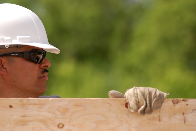 Members of the 433rd Civil Engineering Squadron conduct a humanitarian mission in the Red Lake Indian Reservation for the Red Lake band of Chippewa Indians, just outside of Bemidji, Minnesota. Tech. Sgt. Frank Mora, 433rd CES, carries a sheet of plywood which will be used for the subfloor in a home. (U.S. Air Force photo/Airman 1st Class Brian McGloin)