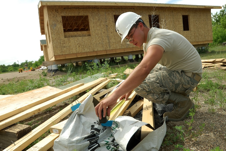 Members of the 433rd Civil Engineering Squadron conduct a humanitarian mission in the Red Lake Indian Reservation for the Red Lake band of Chippewa Indians, just outside of Bemidji, Minnesota. Senior Airman Jaime Payen, 433rd CES electrician, measures a length of framing lumber to use in an installation of an electrical panel. The board, a scrap piece from framing one of the houses in the background, happened to be exactly the right size. (U.S. Air Force photo/Airman 1st Class Brian McGloin)