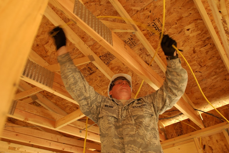 Members of the 433rd Civil Engineering Squadron conduct a humanitarian mission in the Red Lake Indian Reservation for the Red Lake band of Chippewa Indians, just outside of Bemidji, Minnesota. Master Sgt. Curtis Wilson runs wire over ceiling joists from an electrical panel to where a bathroom ceiling fan will be.(U.S. Air Force photo/Airman 1st Class Brian McGloin)