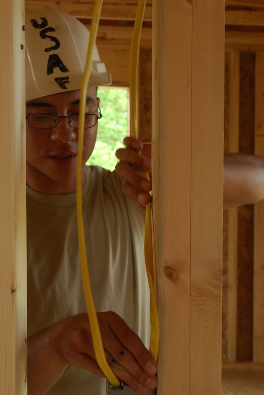 Members of the 433rd Civil Engineering Squadron conduct a humanitarian mission in the Red Lake Indian Reservation for the Red Lake band of Chippewa Indians, just outside of Bemidji, Minnesota. Senior Airman Jaime Payen, an electrician from the 433rd Civil Engineering Squadron, installs wire for electricity for lights and electrical sockets.(U.S. Air Force photo/Airman 1st Class Brian McGloin)