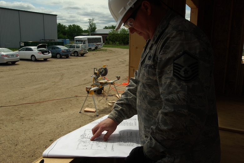 Members of the 433rd Civil Engineering Squadron conduct a humanitarian mission in the Red Lake Indian Reservation for the Red Lake band of Chippewa Indians, just outside of Bemidji, Minnesota. Master Sgt. Curtis Wilson, 433rd Civil Engineering Squadron electician, reviews plans of a house under construction.(U.S. Air Force photo/Airman 1st Class Brian McGloin)
