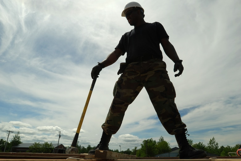Members of the 433rd Civil Engineering Squadron conduct a humanitarian mission in the Red Lake Indian Reservation for the Red Lake band of Chippewa Indians, just outside of Bemidji, Minnesota. Tech. Sgt. Mark Johnson, 433rd CES, holds the hammer he uses to align the sheets of plywood used for the subfloor.(U.S. Air Force photo/Airman 1st Class Brian McGloin)