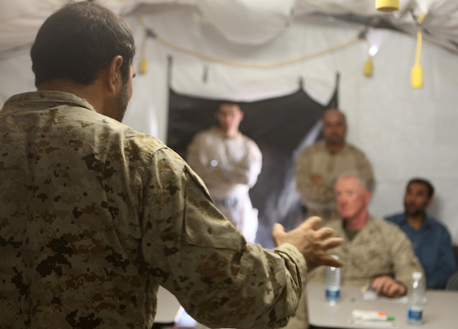 A Pashto linguist speaks to Regional Command Southwest commander Maj. Gen. Richard P. Mills, during a security conference at Forward Operating Base Sher Wali, Marjah, Helmand province, Afghanistan, June 29, 2010. The meeting was held to discuss the emergence of the Afghan Uniform Police in Marjah, which is slated to replace the Afghan National Civil Order Police as the area's local police force in the near future. Attending the event were Mills; Helmand provincial governor, Mohammad Gulab Mangal; Marjah's district governor, Haji Zahir and other high-ranking Marine, ANCOP and Afghan National Army officers.