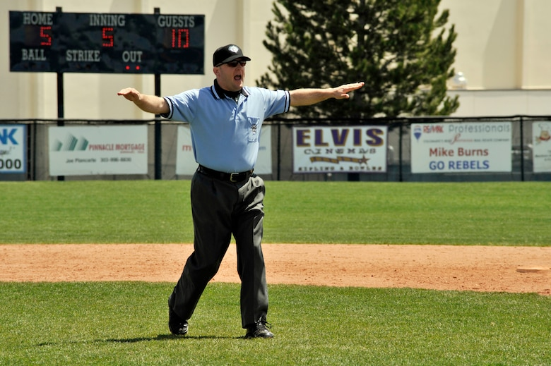 """COLUMBINE, Colo. -- Staff Sgt. Larry Bouchard, Air Force Intelligence, Surveillance, and Reconnaissance Agency Detachment 45 Satellite Operations non-commissioned officer-in-charge, gives the """"safe"""" signal during a local high school varsity baseball game May 1. Sergeant Bouchard is certified through the National Federation of State High School Associations and has been umpiring for the last four years. (U.S. Air Force photo by Staff Sgt. Kathrine McDowell)"""