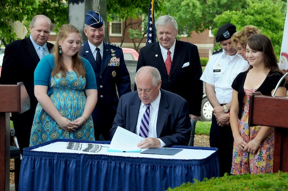 Illinois Gov. Pat Quinn signs the Intestate Compact on Education Opportunity for Military Children into law June 28, 2010, at Scott Air Force Base, Ill. Witnessing the signature are Illinois State Rep. Thomas Holbrook, family member Claire Krebs, commander of U.S. Transportation Command Gen. Duncan J. McNabb, Senior State Liaison for the Department of Defense Thomas Hinton, Adjutant General of the Illinois National Guard Maj. Gen. William Enyart, State Sen. Deanna Demuzio and family member Breanna Bence. (U.S. Transportation Command photo/Bob Fehringer)
