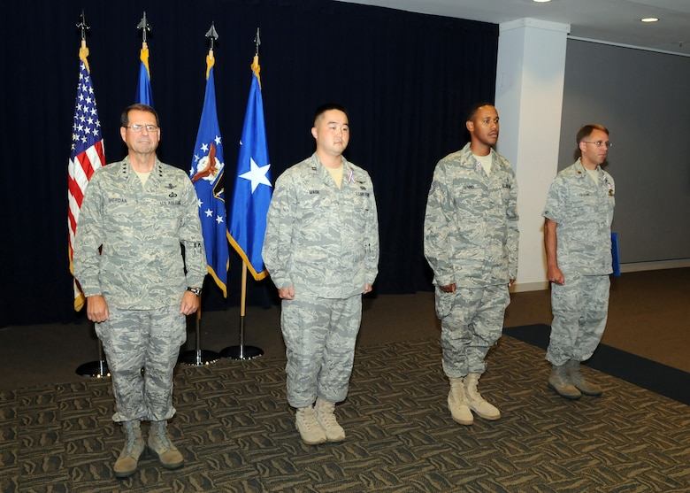 Three Airmen receive medals for their service while deployed during the recent Welcome Home Ceremony, June 23. Pictured from left to right are:  Lt. Gen. Tom Sheridan, SMC commander; Tech Sgt. Terance Dennis, 61st Medical Group; Maj. Jeffrey Gibson, 61st Contracting Squadron; and Capt. Peter Mask, Global Positioning Systems Wing. (Photo by Jim Gordon)