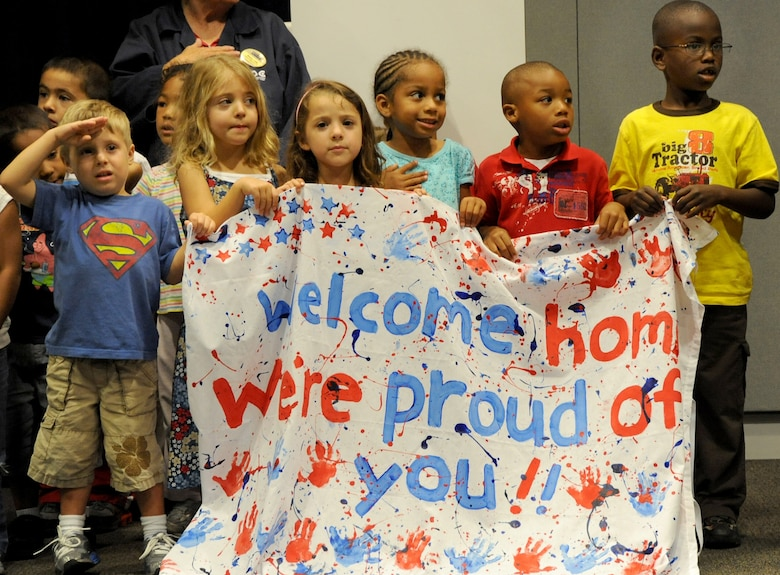 Children from the Los Angeles AFB Child Development Center salute returning Airmen at the recent Welcome Home Ceremony, June 23. The children sang the National Anthem during the ceremony. (Photo by Lou Hernandez)