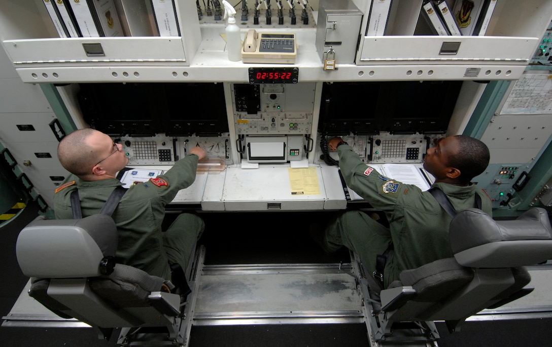 """MINOT AIR FORCE BASE, N.D. -- 1st Lt. Jeremy King (left) and 2nd Lt. Glen Jasper (right), both from the 740th Missile Squadron, simulate launching a Minuteman III intercontinental ballistic missile at the missile procedure trainer here Sept. 24, 2009. The professionalism of the 740th MS crew commanders played an integral part in missile alert facility E-01 winning the Maj. Gen. M. C. """"Tim"""" Padden Award for best Missile Alert Facilities in Air Force Space Command for 2009. (U.S. Air Force photo by Senior Airman Matthew Smith)"""