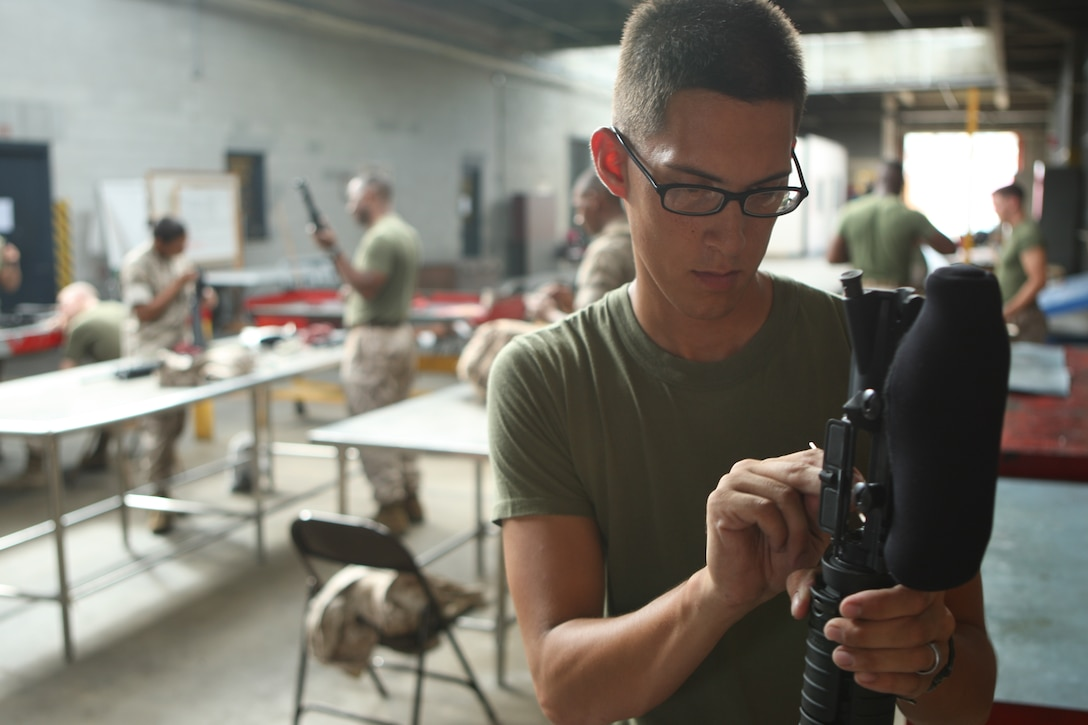 Marines with Headquarters and Support Battalion, Marine Corps Base Camp Lejeune, clean their weapons at the armory after firing on the rifle range, recently.