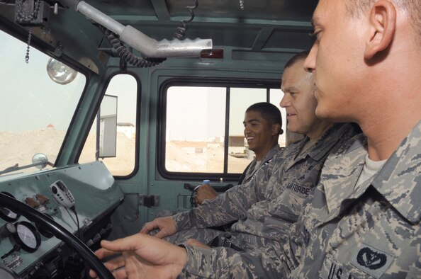 Senior Airman Joshua Thompson explains the operation of a P-19 crash fire truck to Chief Master Sgt. of the Air Force James A. Roy and Staff Sgt. Delavar McKee June 27, 2010, at a base in Southwest Asia. Airman Thompson is a firefighter driver operator with the 380th Expeditionary Civil Engineer Squadron. (U.S. Air Force photo/Tech. Sgt. April Wickes)