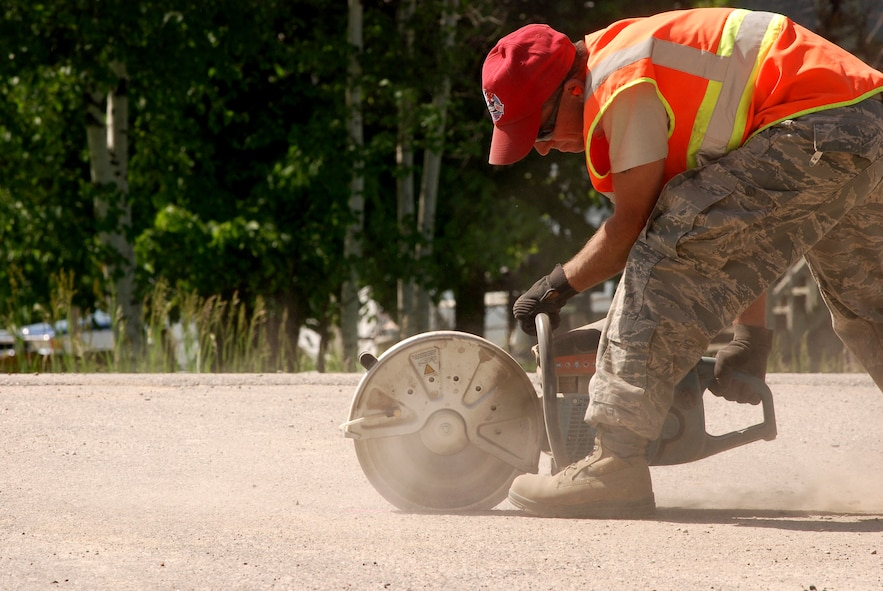 A member of the 560th RED HORSE Squadron from Charleston Air Force Base, South Carolina, cuts a section of ashphalt as part a humanitarian mission in the Red Lake Indian Reservation for the Red Lake band of Chippewa Indians, just outside of Bemidji, Minnesota. (U.S. Air Force photo/Airman 1st Class Brian McGloin)