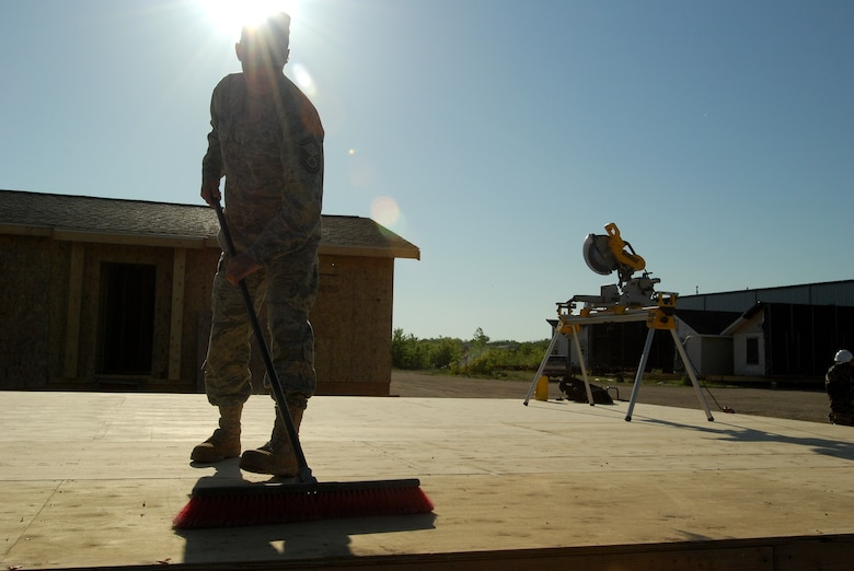 Members of the 433rd Civil Engineering Squadron conduct a humanitarian mission in the Red Lake Indian Reservation for the Red Lake band of Chippewa Indians, just outside of Bemidji, Minnesota. Senior Master Sgt. Michael Barnes, 433rd CES, sweeps the subfloor before the framing forthe walls begins. (U.S. Air Force photo/Airman 1st Class Brian McGloin)