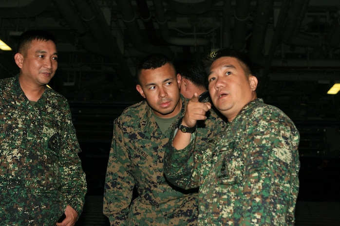 Maj. Niel Estrella, a civil military operations officer with the Philippine Marines Corps, and Capt. Richard McKenzie, an assistant operations officer with Battalion Landing Team 2nd Battalion, 7th Marines (BLT 2/7), 31st Marine Expeditionary Unit (MEU), discuss information about a landing craft unit (LCU), in the well deck aboard the forward-deployed amphibious assault ship USS Essex (LHD 2), March 1. The MEU recently completed Exercise Cobra Gold 2010 (CG '10) and is currently scheduled to go underway to the Republic of the Philippines in support of Exercise Balikatan 2010 (BK '10). (Official Marine Corps photo by Lance Cpl. Dengrier M. Baez)