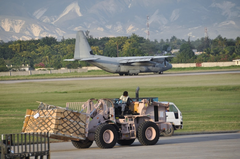 A C-130 Hercules lands behind an Airman unloading cargo with a 10K forklift at Toussaint Louverture International Airport in Haiti.  Aerial porters from the 621st Contingency Response Wing handled approximately 1 million lbs of cargo a day throughout the deployment. (U.S Air Force photo/Capt. Dustin Doyle)