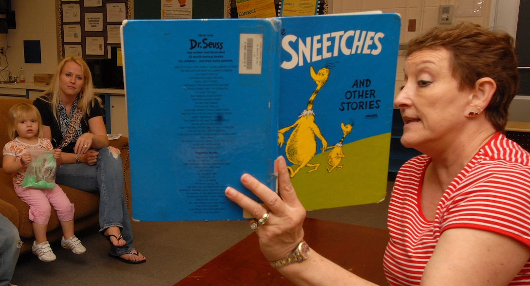 "Nancy Speer (left), a Kadena Elementary School literacy specialist, reads ""Sneeches"" by Dr. Seuss to Tayson, Tatum and Kara Barney during the school's birthday tribute to the famous author March 2. Dozens of students and parents read books, played computer learning games and ate green eggs and ham. (Air Force photo/Staff Sgt. Jason Lake)"