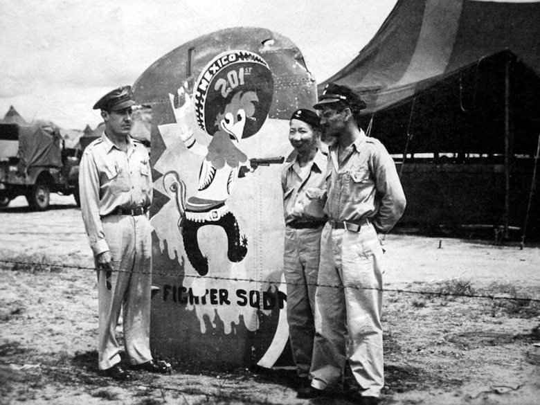 "U.S. Air Force, Philippine Army and Mexican Air Force members admire the representation of ""Panchito Pistoles"", the mascot of the Escuadrón 201, painted on a wing fragment of a Japanese aircraft. ""Panchito Pistoles"" stared in the Walt Disney film ""The Three Caballeros"" and was adopted by their unit. (Courtesy photo)"